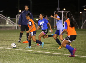 Guam U16 Women's national team head coach Brett Maluwelmeng (in background) watches as Skyylerblu Johnson carries the ball toward the goal facing some defensive pressure from other players in a recent open tryout session for the team at the Guam Football Association National Training Center.
