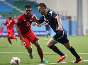 Guam's John Matkin sprints to lose Singapore's Zulfahmi Arifin on defense during a FIFA international friendly at the Jalan Besar Stadium in Singapore Tuesday. Both teams battled to a 2-2 draw.