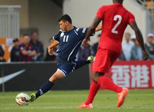 Guam's Dylan Naputi prepares to take a shot ahead of Hong Kong's Baise Festus in a FIFA international friendly match at Mong Kok Stadium in Hong Kong Saturday. Hong Kong escaped with a 1-0 win.