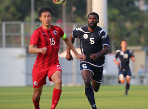 Guam's Brandon McDonald engages in a foot race to the ball with Hong Kong captain Chan Wai Ho in a FIFA international friendly match at Mong Kok Stadium in Hong Kong Saturday. Hong Kong escaped with a 1-0 win.