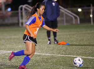 Guam U16 Women's national team head coach Brett Maluwelmeng (in background) watches as Hopemary Calip prepares to kick the ball toward the goal during a recent open tryout session for the team at the Guam Football Association National Training Center.