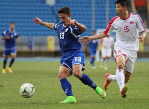 Guam's Ryan Guy maneuvers to get around the defense of DPR Korea's Ri Yong Chol en route to the goal during a semifinal round match of the EAFF East Asian Cup at the Taipei Municipal Stadium in Chinese Taipei.