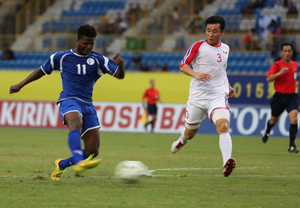 Guam's Shane Malcolm takes a shot on goal ahead of DPR Korea defender Jang Song Hyok during a semifinal round match of the EAFF East Asian Cup at the Taipei Municipal Stadium in Chinese Taipei.