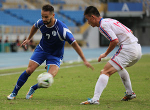 Guam's John Matkin begins to make his move to the goal facing defensive pressure from DPR Korea's So Hyon Uk during a semifinal round match of the EAFF East Asian Cup at the Taipei Municipal Stadium in Chinese Taipei.