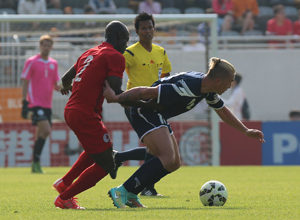 Guam captain Jason Cunliffe gets pulled back by Hong Kong's Baise Festus while trying to advance the ball in the midfield in a FIFA international friendly match at Mong Kok Stadium in Hong Kong Saturday. Hong Kong escaped with a 1-0 win.