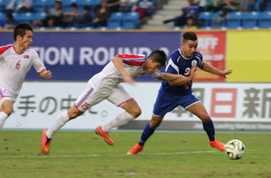 DPR Korea's Ro Hak Su (No. 6) and Ri Yong Chol (No. 15) chase Guam's Marcus Lopez to try to prevent him from shooting during a semifinal round match of the EAFF East Asian Cup at the Taipei Municipal Stadium in Chinese Taipei.