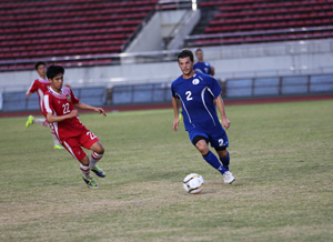 The Matao's Erik Ustruck brings the ball around the defense of Laos' Manolom Phomsouvanh during a FIFA international friendly match against Laos. Guam drew 1-1 with Laos.