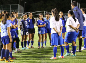 Guam U16 Women's national team head coach Brett Maluwelmeng (in blue jacket) shares his observations with players during a recent open tryout session for the team at the Guam Football Association National Training Center.