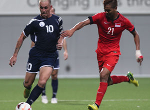 Guam captain Jason Cunliffe advances the ball forward facing defensive pressure from Singapore's Safuwan Baharudin during a FIFA international friendly at the Jalan Besar Stadium in Singapore Tuesday. Both teams battled to a 2-2 draw.