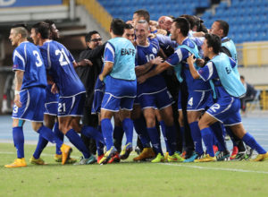 Matao players and staff mob captain Jason Cunliffe (No. 10) after he scored the equalizing goal against DPR Korea in the 58th minute during a semifinal round match of the EAFF East Asian Cup at the Taipei Municipal Stadium in Chinese Taipei.
