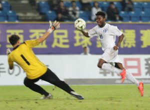 Guam's Shane Malcolm successfully chips the ball up over Chinese Taipei goalkeeper Lu Kun Chi to score the eventual game-winner during an opening day match of the EAFF East Asian Cup semifinal round at the Taipei Municipal Stadium in Taipei City. Guam defeated Chinese Taipei 2-1.
