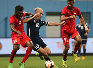 Guam captain Jason Cunliffe gets held back by Singapore's Hariss Harun as Safuwan Baharudin (21) converges on the pair for support during a FIFA international friendly at the Jalan Besar Stadium in Singapore Tuesday. Both teams battled to a 2-2 draw.