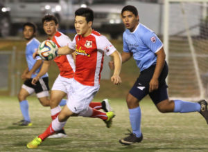The Payless Supermarkets Strykers FC's Min Sung Choi sprints to gain possession of the ball as teammate Dylan Naputi provides support during a 2014-2015 Budweiser Soccer League Division I match against the Paradise Fitness Sidekicks.