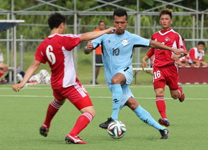 The Northern Mariana Islands' Jonathan Takano attempts to dribble the ball around the defense of Mongolia's Amgalan Chinzorig in an opening day match of the EAFF East Asian Cup Round 1 at the Guam Football Association National Training Center. Mongolia defeated NMI 4-0.